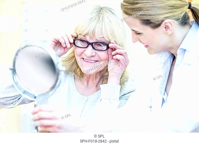 Optometrist counselling senior woman in optometrist's shop