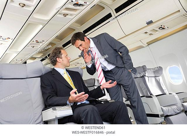 Germany, Bavaria, Munich, Businessmen whispering in business class airplane cabin
