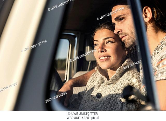 affectionate couple sitting in their camper with arms around, watching sunset