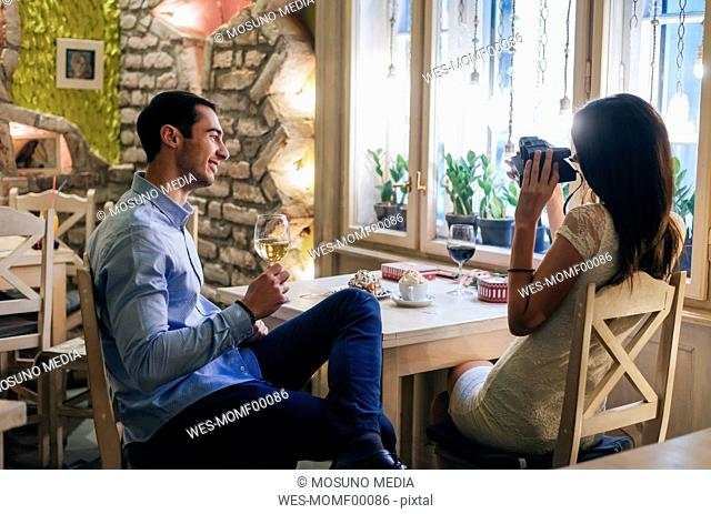 Young couple taking instant photos in a restaurant