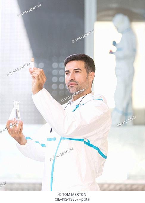 Scientist in clean suit examining liquid in test tube