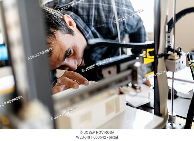 Worker controlling a model, 3D printer