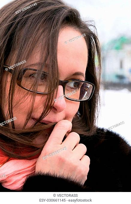Woman wearing glasses with a playful gaze warming up her hand, outdoor horizontal shot