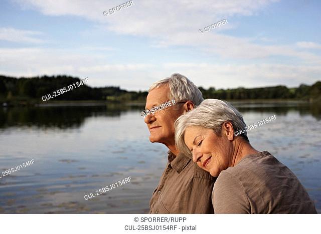 Senior woman lying head on mans shoulder