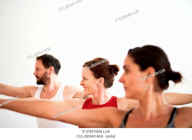 People in exercise studio arms open in yoga position