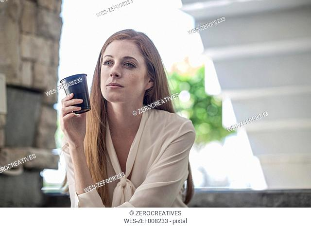Young tired businesswoman drinking coffee