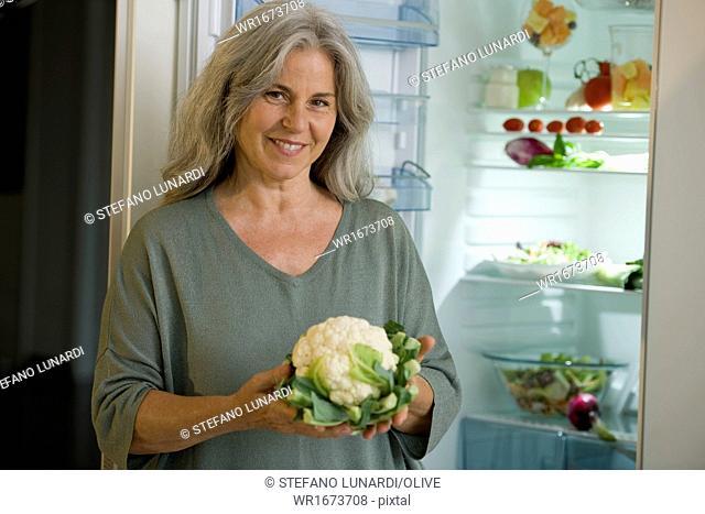 Mature woman holding cauliflower