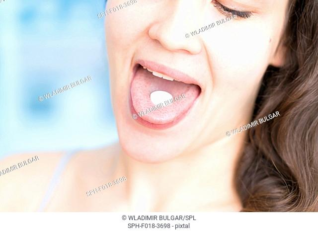 Woman with white pill on tongue