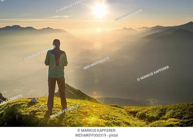 Austria, Tyrol, hiker looking at distance at sunrise