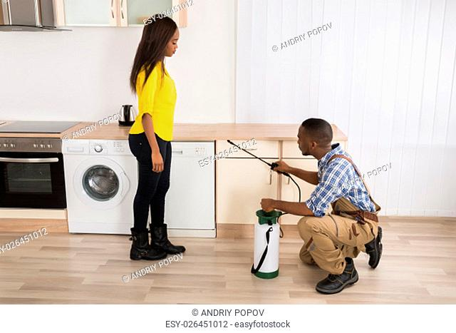 Woman Looking At Male Worker Spraying Pesticides On Wooden Drawer