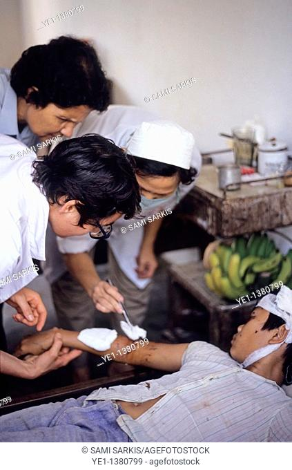 Wounded boy being treated by a nurse at Nam Dong hospital, Vietnam