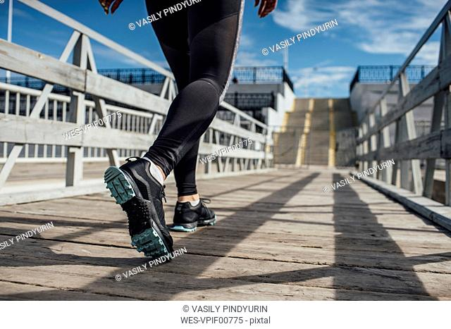 Legs of athletic woman running on a pier