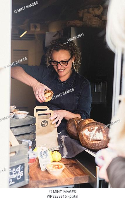 Smiling woman wearing glasses placing freshly baked pie in brown paper shopping bag