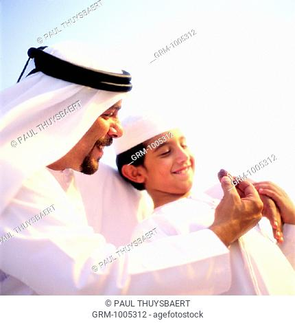 Arab father offering his son a dried date (dates are eaten to break the fast in the evening during Ramadan)