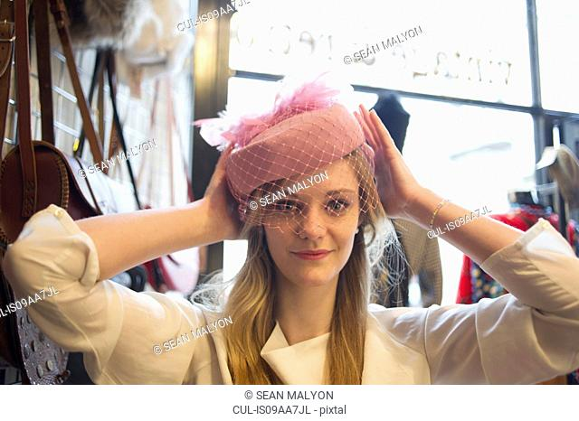 Woman trying on vintage hat