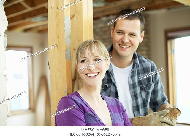 happy, mid adult couple in renovation