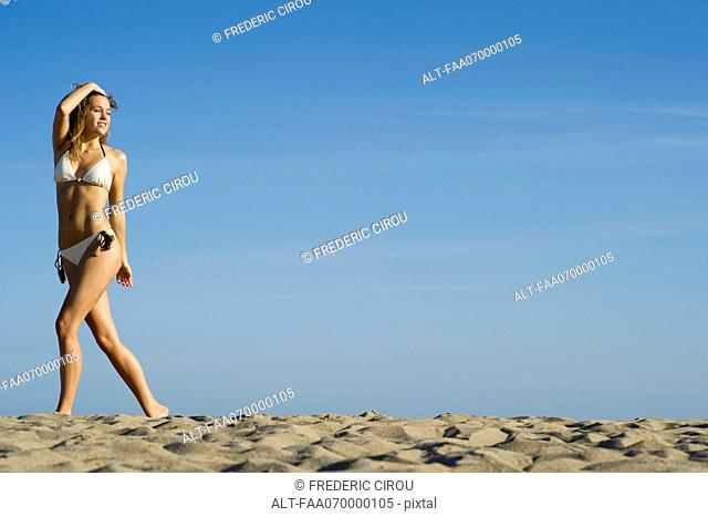 Woman in bikini walking at the beach