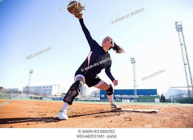 Female baseman catching the ball during a baseball game