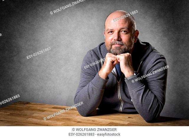 Portrait of a friendly looking, balding and unshaven man sitting on a wooden table