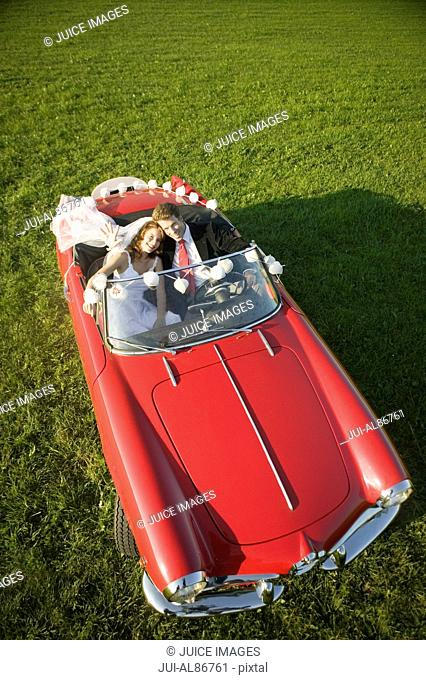 Newlyweds driving car in field
