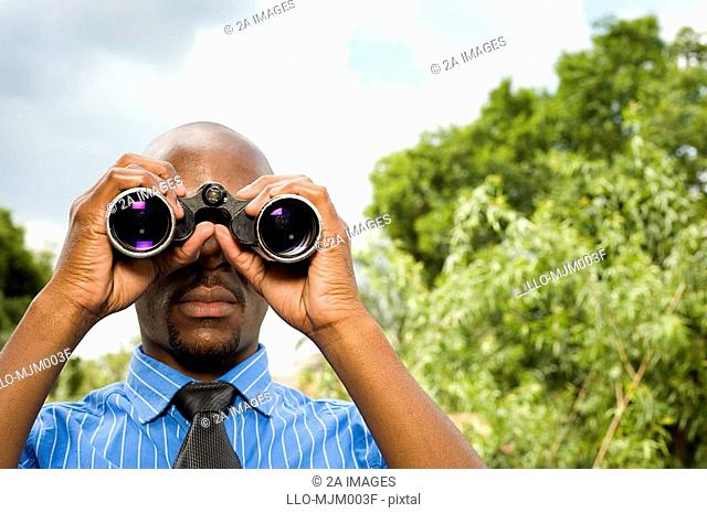 Businessman outdoors, looking through binoculars into camera. Pretoria, South Africa