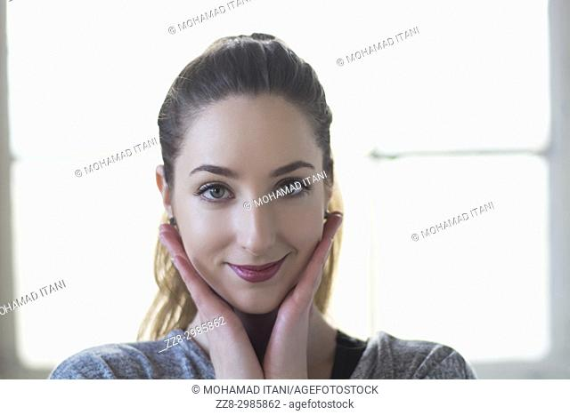 Beautiful young woman hands touching face smiling