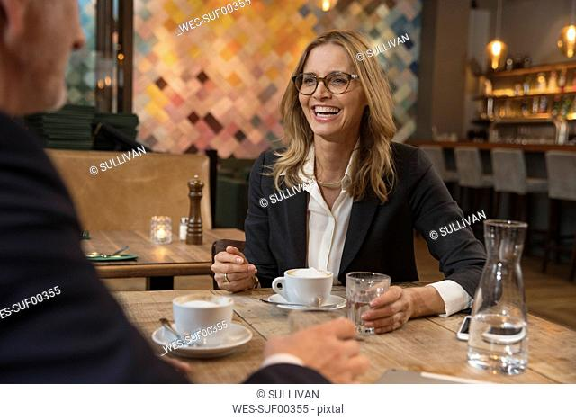 Portrait of laughing businesswoman having meeting in a restaurant