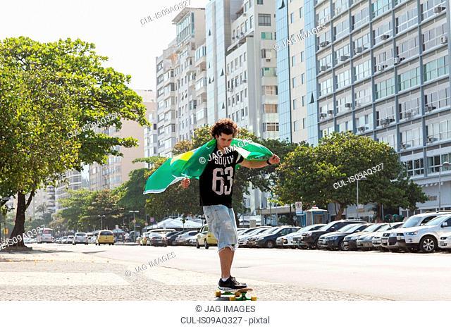 Young man skateboarding holding Brazilian flag, Copacabana, Rio De Janeiro, Brazil
