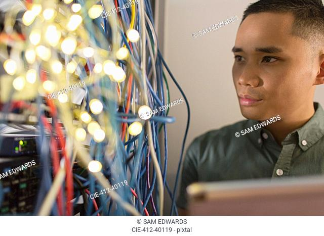 Focused male IT technician examining wires on server panel
