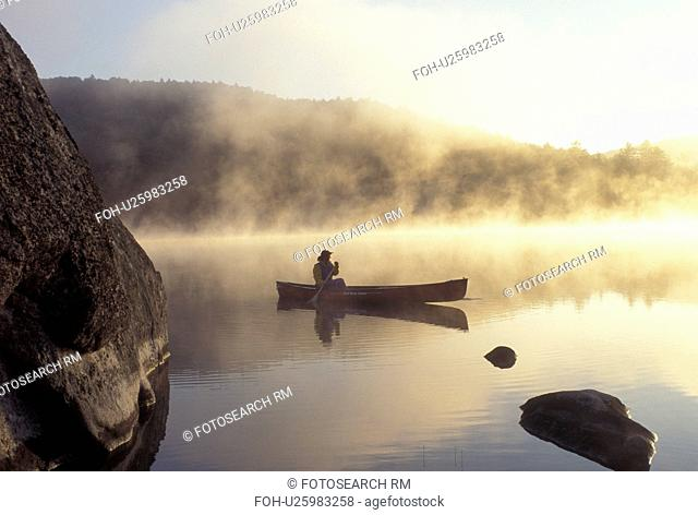 canoeing, canoe, Vermont, VT, Woman paddles a canoe on Kettle Pond in the mist in Groton State Forest
