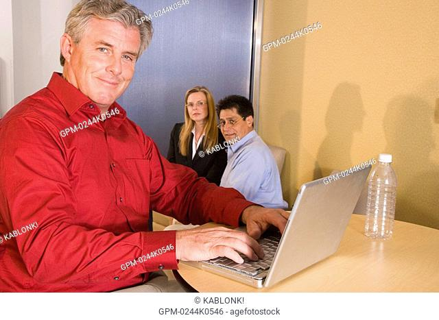 Portrait of three multi-ethnic businesspeople sitting in office, focus on man using laptop in foreground