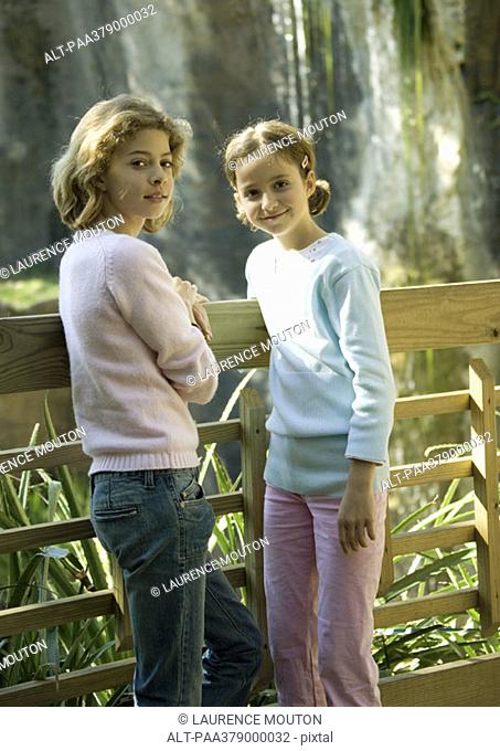 Two girls leaning against wooden fence