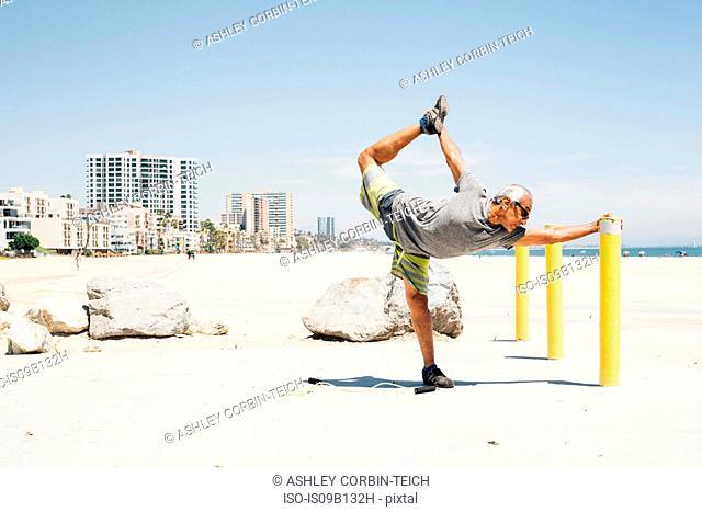 Senior man, exercising on beach, stretching leg, Long Beach, California, USA