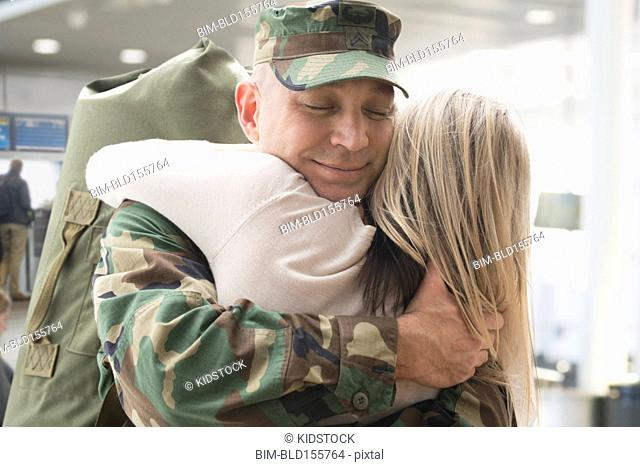 Caucasian returning soldier hugging wife in airport