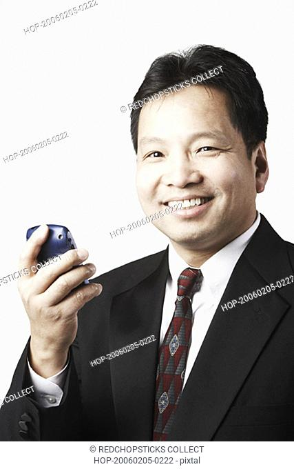 Portrait of a mid adult man holding a mobile phone smiling