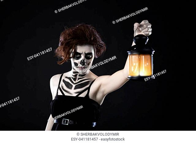 Scary woman with lantern in night scene - Spooky image of a scary woman with dark eyes and appearance of a witch, in a white dress, holding a lit lantern