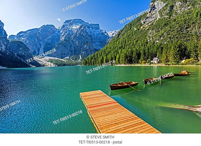 Wooden pier and row boats on Pragser Wildsee in South Tyrol, Italy
