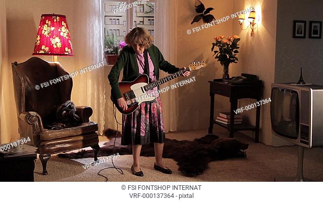 WS of a senior woman rocking out while playing her electric guitar