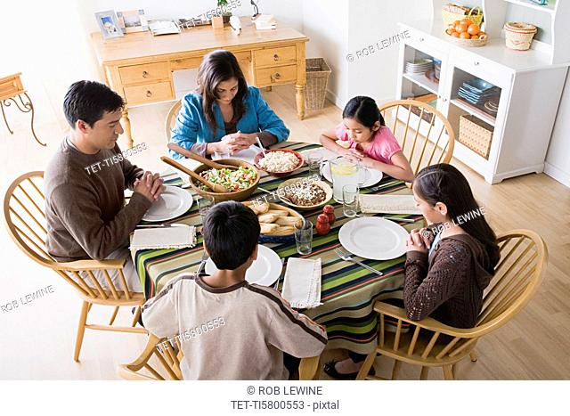 Family with three children 8-9, 10-11 praying at table before dining
