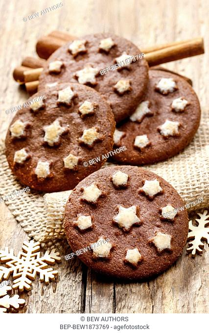 Round chocolate cookies decorated with icing stars