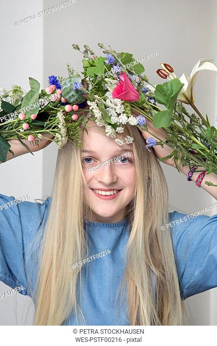 Portrait of smiling blond girl with bunches of flowers