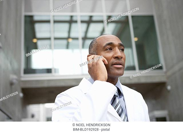 Mixed race doctor talking on cell phone outdoors