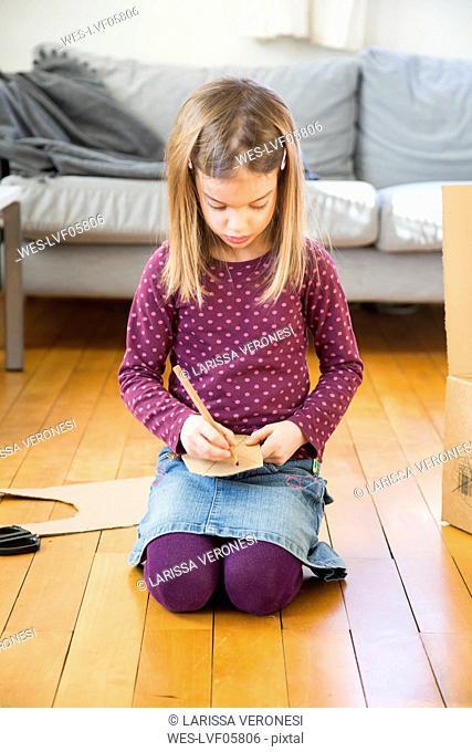 Girl writing with pencil on cardboard