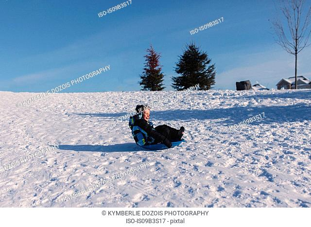 Boy in knit hat tobogganing down snow covered hill