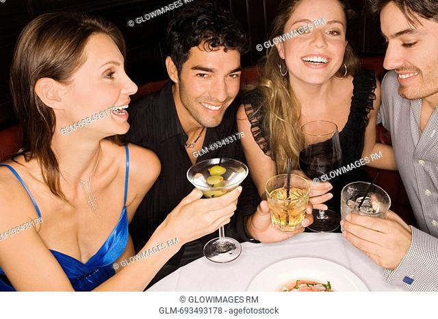 Two young couples sitting at a table and enjoying cocktail