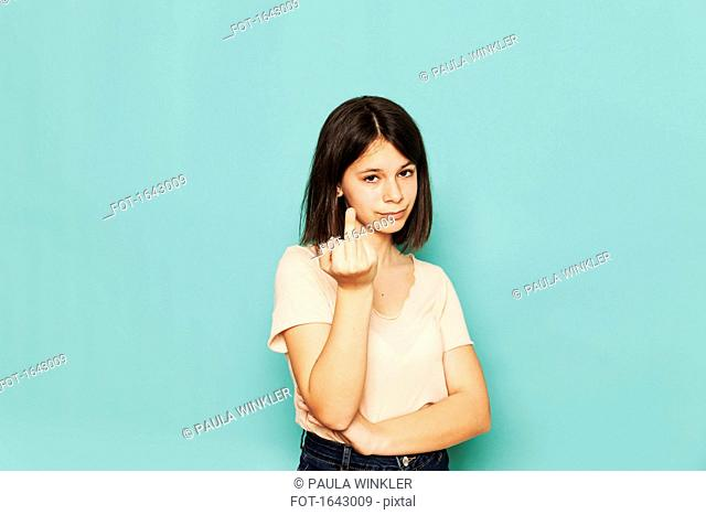 Portrait of rude girl showing middle finger against turquoise background