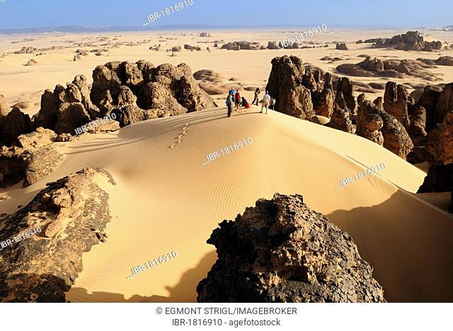Group of tourists, hikers in the sandstone rock formation of Tin Akachaker, Tassili du Hoggar, Wilaya Tamanrasset, Algeria, Sahara desert, North Africa