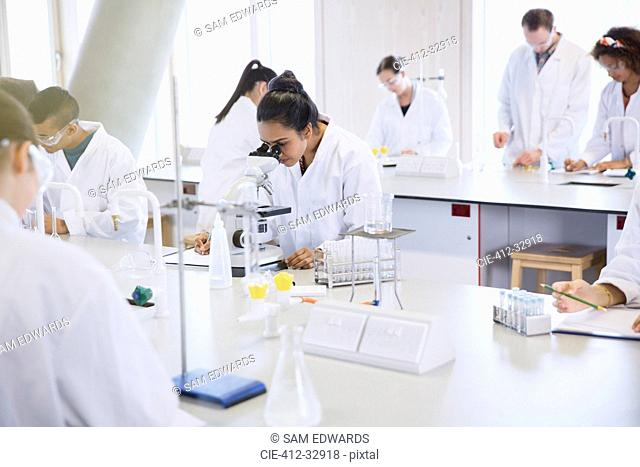 College students using microscope conducting scientific experiment in laboratory