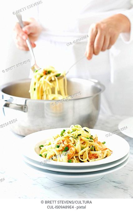 Woman serving linguine