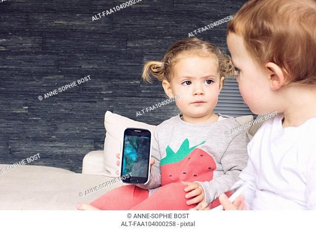Little girl showing smartphone to her brother